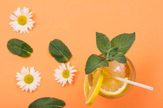 Tall glass of cold refreshing summer lemonade with ice, lemon slices, mint leaves and chamomile flowers on peach colored background. top view