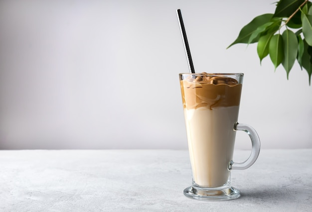 Высокая стеклянная чашка с кофе по-корейски далгона на белом фоне