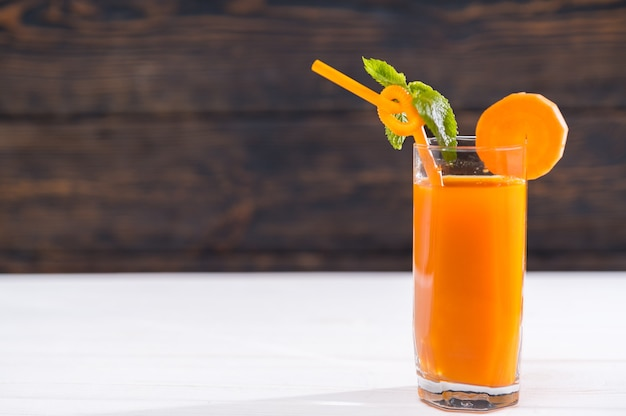 Tall glass of fresh carrot smoothie