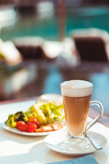 Tall glass of latter coffee on a table in ourdoor area next to swimming pool