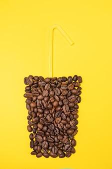 Высокий стакан с кофейными зернами на желтом фоне. вверху - желтая трубочка. вид сверху, копия пространства.