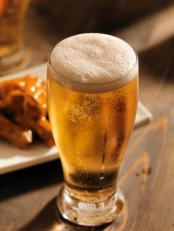 泡立つヘッドが付いているビールの高いガラス