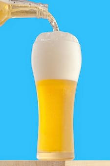 A tall glass with a light chilled beer. beer is poured into a glass.
