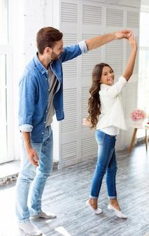 背の高いハンサムな父親は、かわいい10代の娘と一緒に、大きな明るいリビングルームで踊り、笑いながら一緒に楽しんでいます。