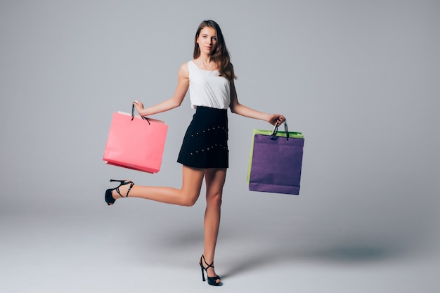 Tall happy girl in shoes with high heels holds leg up and different shopping paper bags isolated on white