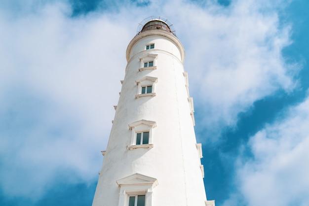 青い曇り空を背景に背の高い灯台タワー