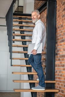 키 큰 남자. 계단에 서 있는 성숙한 키가 큰 중년 남성