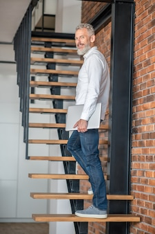 Tall man. mature tall mid-aged man standing on the stairs