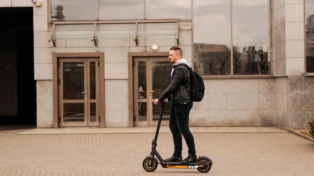 灰色の都市の建物を背景に電動スクーターに乗った背の高い男