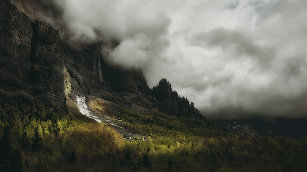 白い厚い雲に覆われた背の高い山