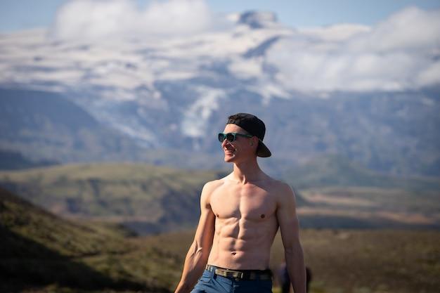 Высокий мускулистый кавказский мужчина с голым торсом стоит на фоне гор и неба, продвигая ...