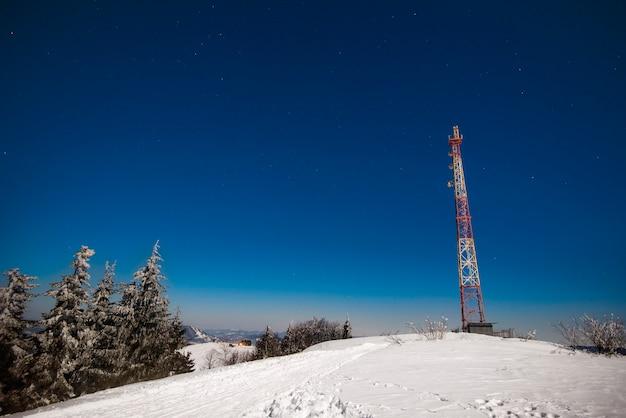 Высокая смотровая башня стоит на заснеженном холме среди хвойного леса со звездной ночью на фоне голубого неба. концепция метеорологической станции. copyspace