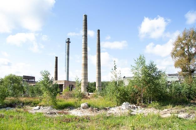 Высокие старые кирпичные трубы бывшего хрустального завода на фоне голубого неба.