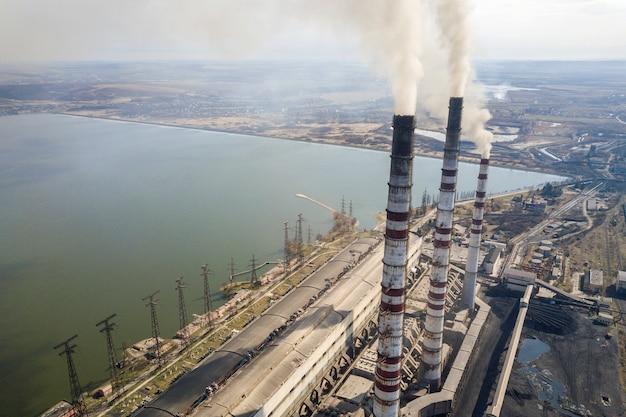Высокорослые трубы электростанции, белый дым на сельском ландшафте, вода озера и голубое небо копируют предпосылку космоса.