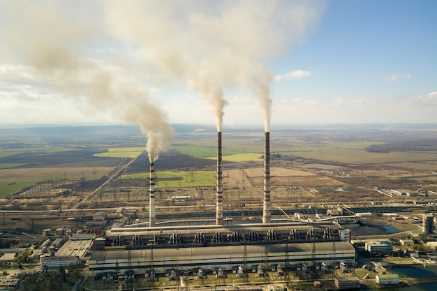 Tall pipes of power plant, white smoke on rural landscape and blue sky