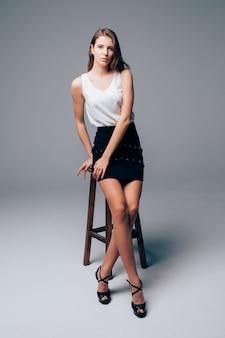 엄격한 고전적인 옷을 입고 키 크고 섹시한 날씬한 갈색 머리 소녀는 흰색 배경 앞의 스튜디오에서 높은 의자에 앉아