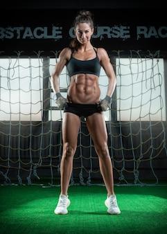 Высокая стройная красивая женщина позирует в тренажерном зале на фоне большого окна.
