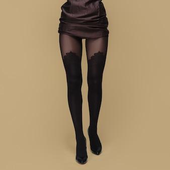 タイツで背の高いスリムな女性の脚。プリント入りのパンスト。