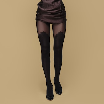 Tall slim female legs in tights. pantyhose with prints.