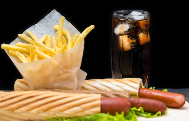 Tall soda glass with ice next to fries in plastic wrap and hotdogs wrapped in bread and lettuce leaves on plate