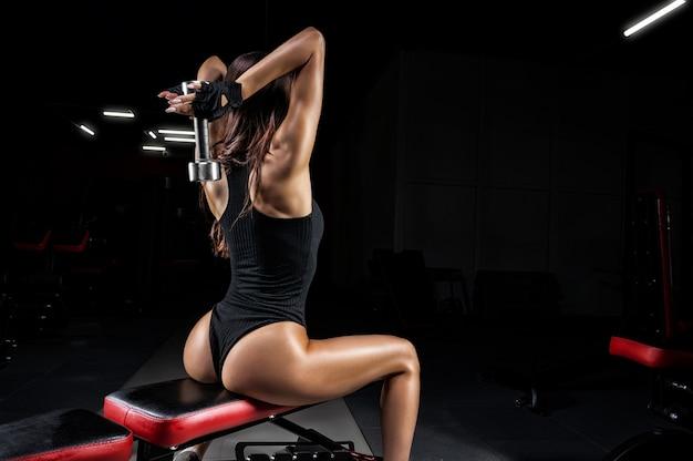 Высокая спортивная женщина выполняет упражнение на скамейке в тренажерном зале с гантелями. вид сзади.