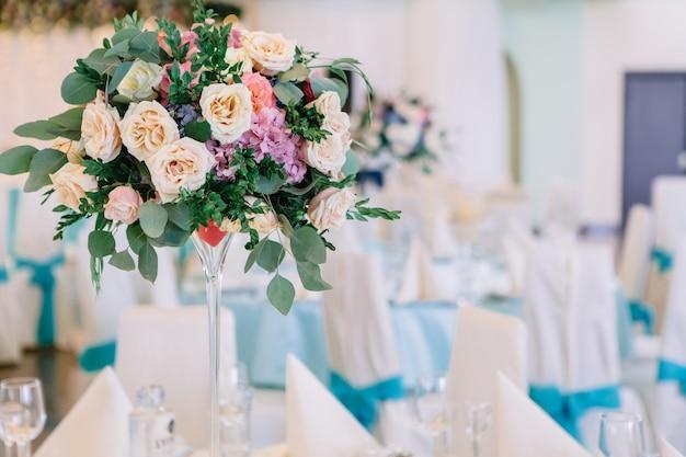 장미와 키 큰 꽃병 식당에서 흰색 테이블에 서
