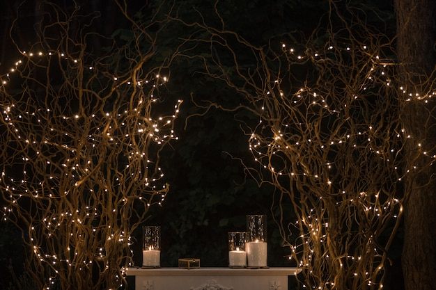 Tall vases with white candles stand under shiny branches