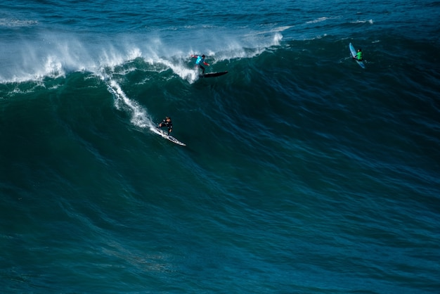 Высокая волна атлантического океана несет серферов к берегу назаре, португалия.