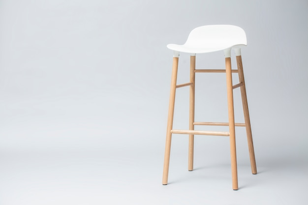 Tall white bar stool legs are wood on gray background