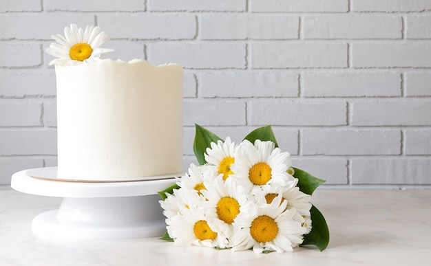 Tall white cake on a stand and a bouquet of daisies.