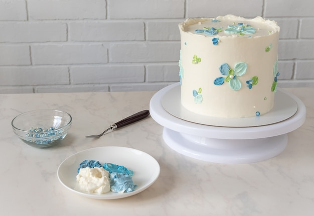 Tall white cake on a stand with cream decor blue flowers and set to decorate and palette knife on table.