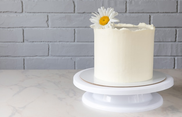 Tall white cake on a stand with a decor of a chamomile flower.