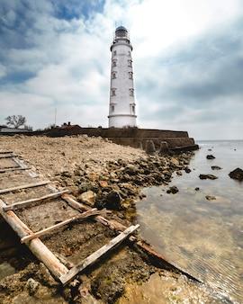 Высокий белый маяк на берегу моря днем летом