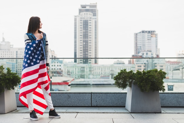 Tall woman on balcony wrapped in american flag