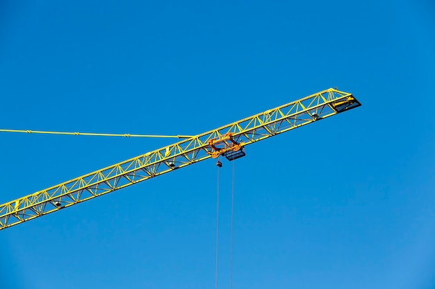 Tall yellow construction crane on a building site for the construction of high rise buildings