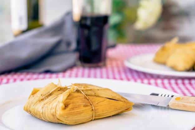タマレは、赤ワインのグラスの横にある伝統的なテーブルの白い皿に盛り付けました。コーンミールと肉の典型的なサンドイッチまたはラテンアメリカ料理。伝統的なアンデス料理。伝統的な食べ物のコンセプト