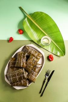 Tamales colombianos, cocina mexicana colombiana, los tamales de la costa, en banana leaf, corn dough stuffed with a stew of pork