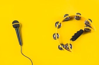 Tambourine with microphone on yellow background
