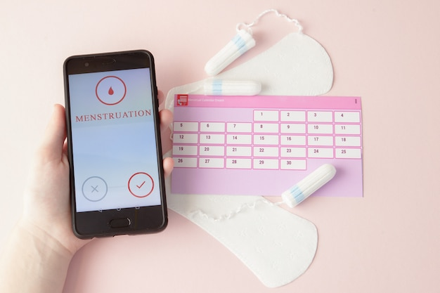 Tampon, feminine, sanitary pads for critical days, feminine calendar, pain pills during menstruation on a pink background. tracking the menstrual cycle and ovulation