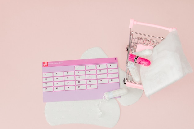 Tampon, feminine, sanitary pads for critical days, feminine calendar, pain pills during menstruation on a pink wall. tracking the menstrual cycle and ovulation