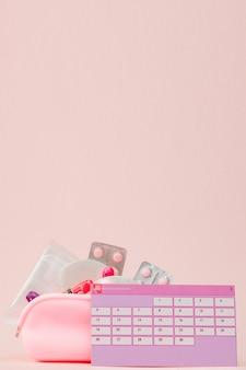 탐폰 및 분홍색 배경에 알 약