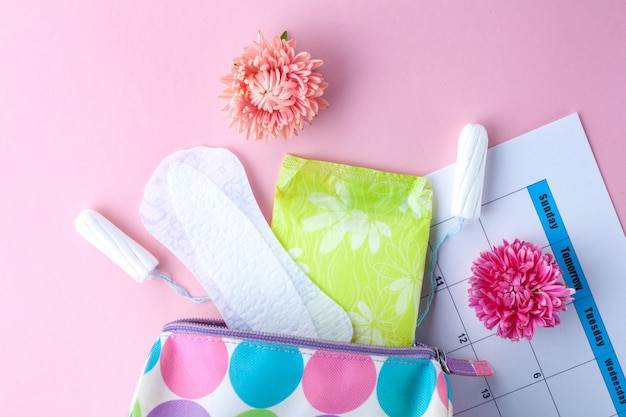 Тампоны, женские гигиенические прокладки, цветы и женская косметичка. гигиенический уход в критические дни. менструальный цикл. забота о здоровье женщин. ежемесячная защита