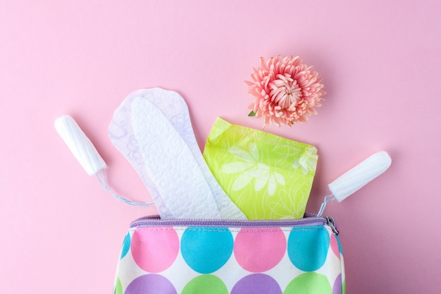 Tampons, feminine sanitary pads, flowers and women's cosmetic bag. hygiene care during critical days. menstrual cycle. caring for women's health.