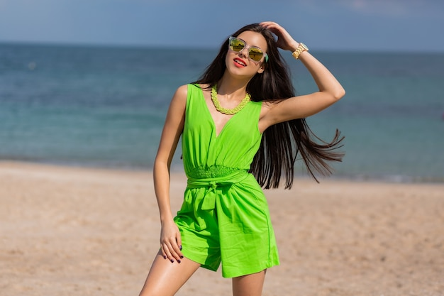 Tan donna sottile corre lungo la spiaggia tropicale. la giovane donna castana si diverte e si gode le sue vacanze estive.