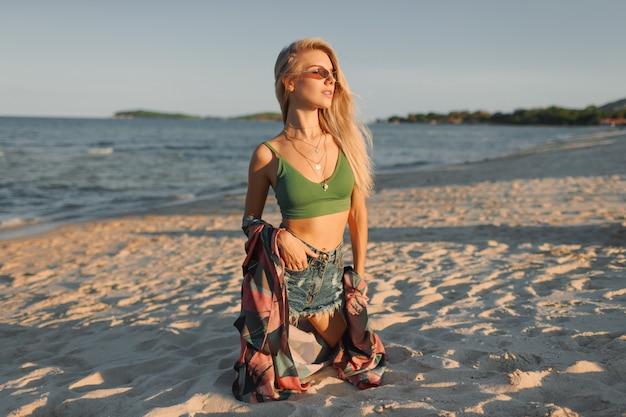 Загорелая стройная женщина с длинными светлыми волосами позирует на тропическом пляже.