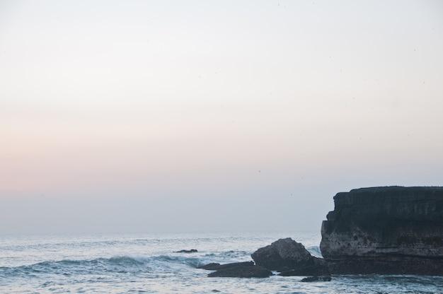 Пляж танах лот и каменный клифт в бали