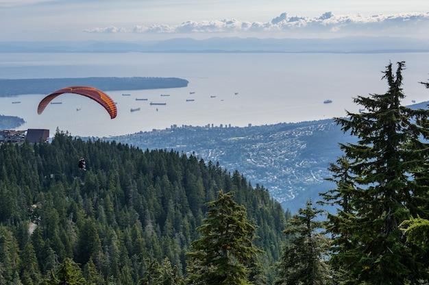 Полет на параплане в тандеме с голубым скольжением и красивыми пушистыми тепловыми облаками на заднем плане. тема для активного отдыха и экстремальных видов спорта.