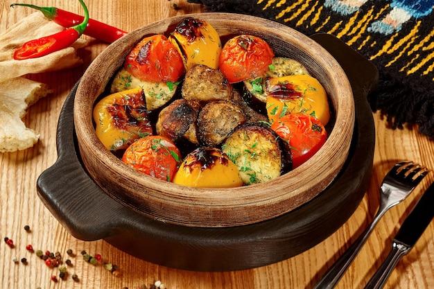 Овощи запеченные в тандыре в деревянной миске с шотис пури Premium Фотографии