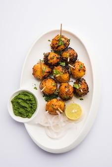 탄두리루는 인도 향신료로 구운 감자입니다. 그린 처트니를 곁들인 파티 에피타이저입니다. 선택적 초점