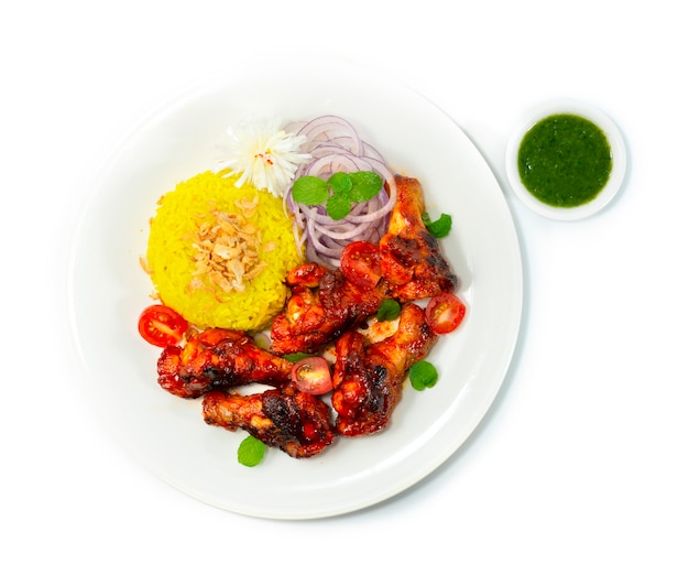Tandoori chicken grilled served mint sauce and biryani rice recipe ontop crispy onion is a classic indian dinner that marinates chicken wing in a creamy yogurt base,